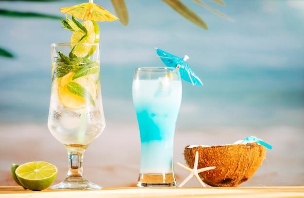 Jasny parasol ozdobiony koktajlami z limonki i mlekiem kokosowym ze słomką