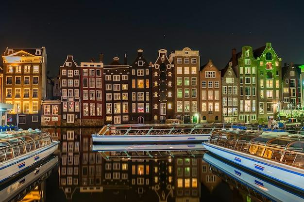 Jasny pejzaż amsterdamu z odbiciem świateł nocnych w wodzie