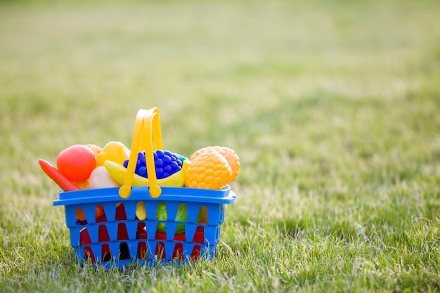 Jasny plastikowy kolorowy kosz z zabawkowymi owocami i warzywami na zewnątrz w słoneczny letni dzień.