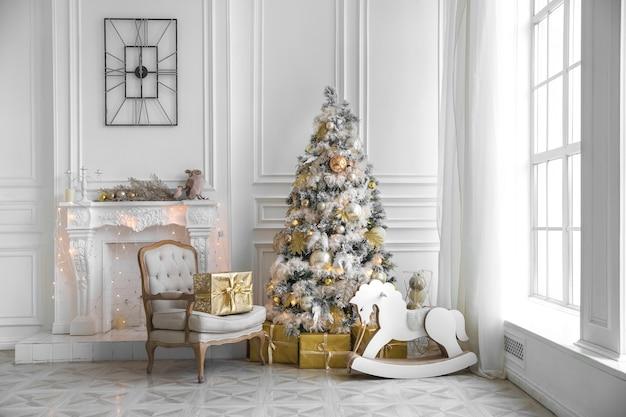 Jasny pokój ze świątecznym wnętrzem choinka ozdobiona świecącą girlandą i złotymi kulkami