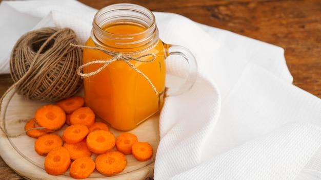 Jasny pomarańczowy sok z marchwi w szklanym słoju i motek sznurka na drewnianym tle. sok i posiekane marchewki. domowy napój z witaminami