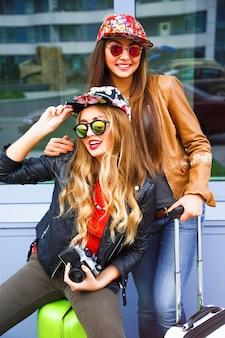 Jasny portret dwóch najlepszych przyjaciółek na świeżym powietrzu, spacerujących z bagażem w pobliżu lotniska, w wygodnych, jasnych stylowych ubraniach, gotowych do podróży i nowych emocji