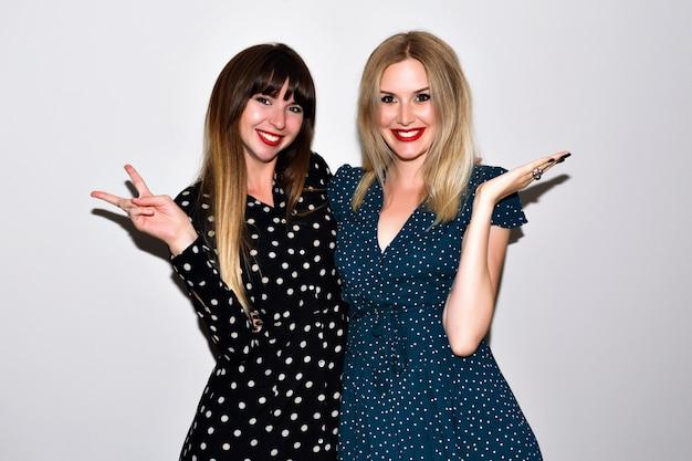 Jasny portret dwóch pięknych przyjaciółek w domu, obejmujący i pokazujący naukę, eleganckie kobiece sukienki i jasny makijaż, styl hipster, pokazujący naukę.