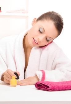 Jasny portret kobiety polerującej paznokcie