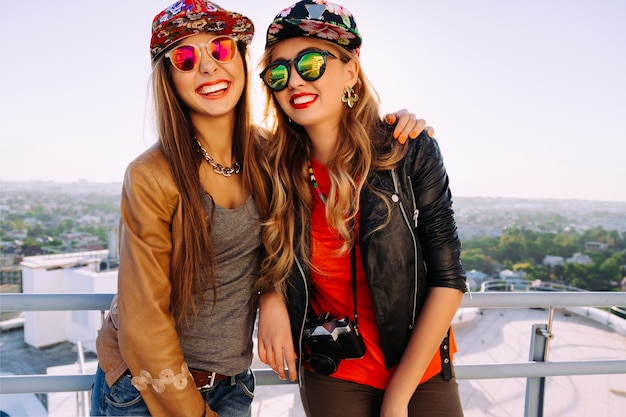 Jasny portret mody na świeżym powietrzu, przedstawiający dwie ładne siostry w stylowych, eleganckich kapeluszach, skórzanej kurtce i okularach przeciwsłonecznych, krzyczących, śmiejących się i dobrze się bawiących.