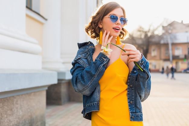Jasny portret pięknej kobiety trzymającej kwiat, żółta sukienka, kurtka dżinsowa, styl hipster, letni trend w modzie, uśmiech, modne okulary przeciwsłoneczne