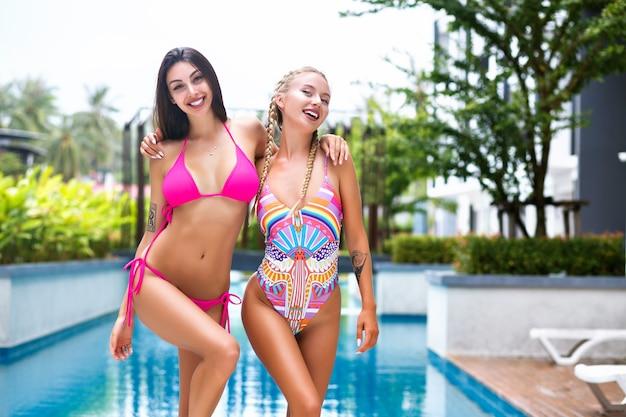 Jasny, pozytywny letni portret pięknych przyjaciółek, pozujących w pobliżu basenu na tropikalnych wakacjach, ubranych w jasne stroje kąpielowe, idealnie smukłe ciało i długie włosy.