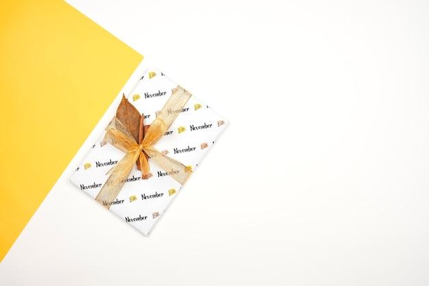 Jasny prezent przewiązany wstążką i cynamonem. listopadowe pudełko na jasne