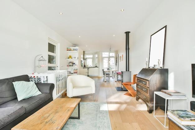 Jasny, przestronny apartament z drewnianą podłogą i prostymi meblami z kominkiem i łóżeczkiem dziecięcym