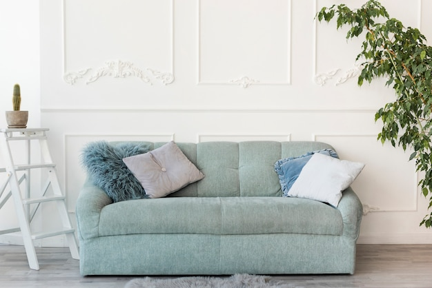 Jasny salon z dużą szarą sofą w centrum