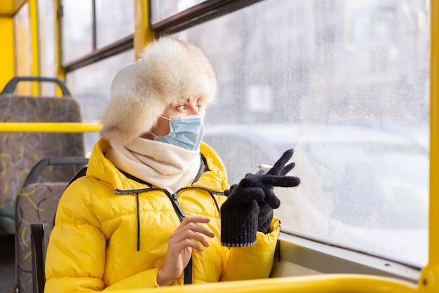 Jasny słoneczny portret młodej kobiety w ciepłych ubraniach w autobusie miejskim w zimowy dzień z telefonem komórkowym w dłoni
