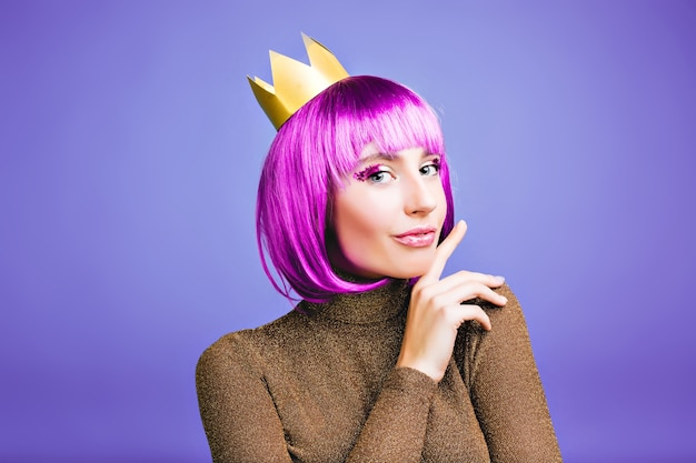 Jasny stylowy portret uroczej młodej kobiety w złotej koronie, krótkie fioletowe włosy. świętowanie nowego roku, wspaniała impreza, pozytywne emocje, luksusowa sukienka, urodziny, karnawał.