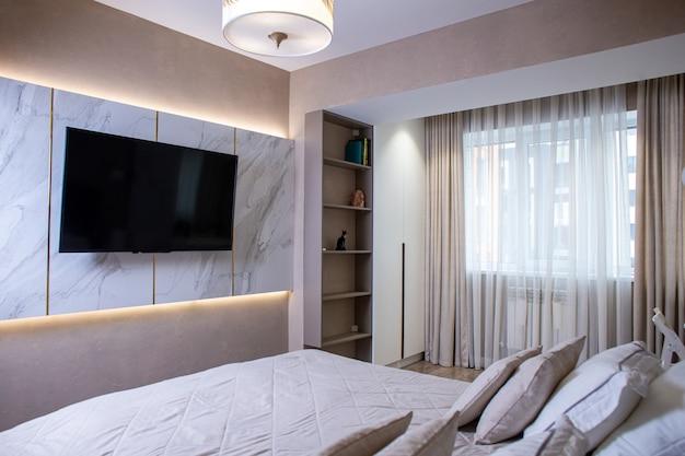 Jasny stylowy wystrój wnętrza w sypialni z telewizorem na ścianie.