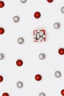 Jasny świąteczny układ z błyszczącymi czerwonymi i srebrnymi kulkami oraz małym pudełkiem upominkowym z błyszczącą kokardką