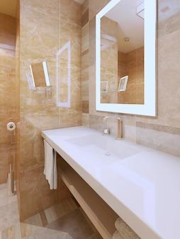 Jasny trend łazienkowy i bursztynowa płytka ze śnieżnobiałym blatem konsoli zlewu i lusterkami z oświetleniem ramy.