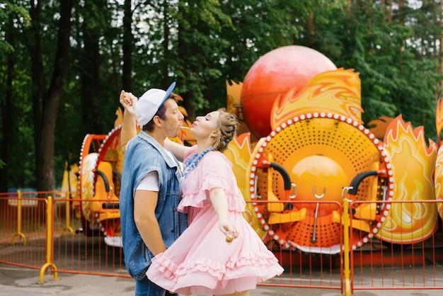 Jasny wesoły para zakochanych odpoczynku w parku rozrywki i przejażdżki