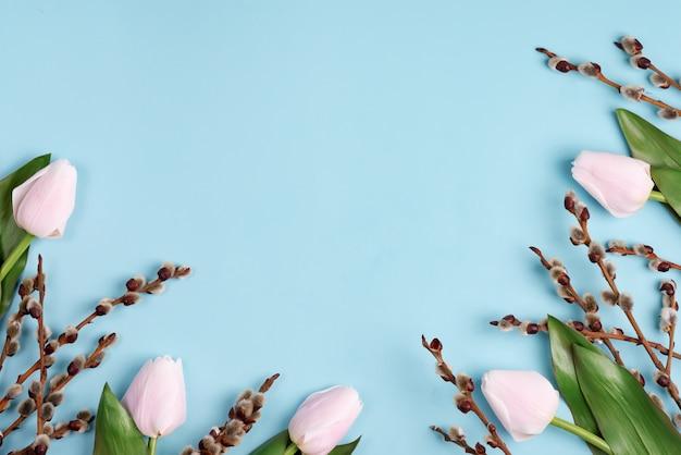 Jasny wiosenny bukiet tulipanów i gałęzi wierzby cipki na niebiesko.
