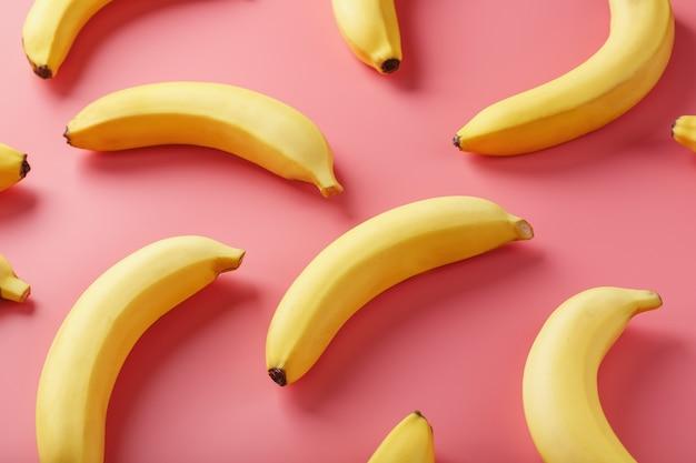 Jasny wzór żółtych bananów na różowym tle.