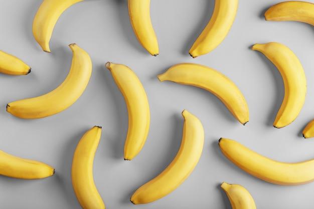 Jasny wzór żółtych bananów na szarej powierzchni