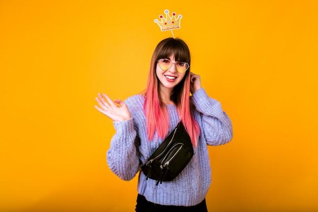 Jasny zabawny portret wesołej hipster kobiety z jasnoróżowymi włosami, ubrana w przytulny sweter, trzymająca fałszywą koronę i uśmiechnięta, gotowa na imprezę, żółta ściana.