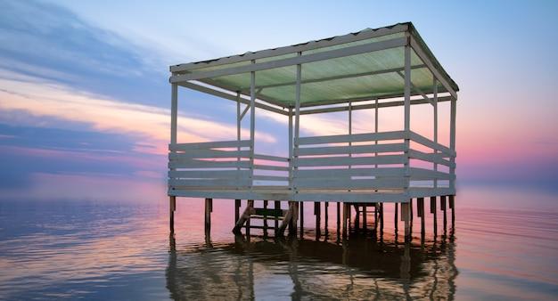 Jasny zachód słońca i domek na wodzie.
