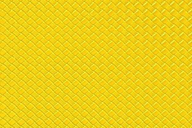 Jasny żółty skórzany tło z imitacją wyplata teksturę. błyszcząca struktura ze sztucznej skóry.