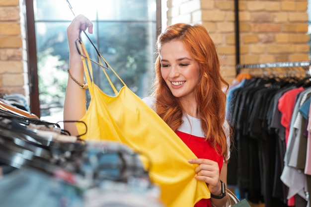 Jasny żółty. wesoła, uśmiechnięta młoda kobieta czuje się szczęśliwa i uważnie przygląda się żółtym ubraniom w modnym sklepie