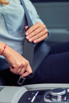 Jazda bezpiecznie przycięte zdjęcie kobiety siedzącej za kierownicą swojego samochodu i zapinającej siedzenie