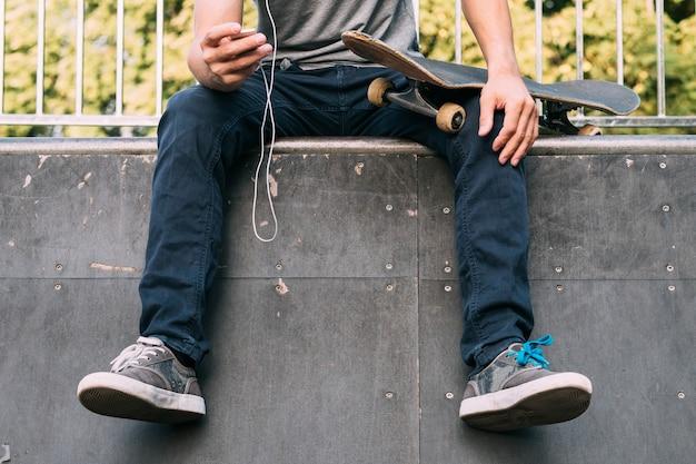 Jazda na deskorolce i relaks przy muzyce. facet siedzi na rampie z deskorolką i odtwarzaczem multimedialnym.