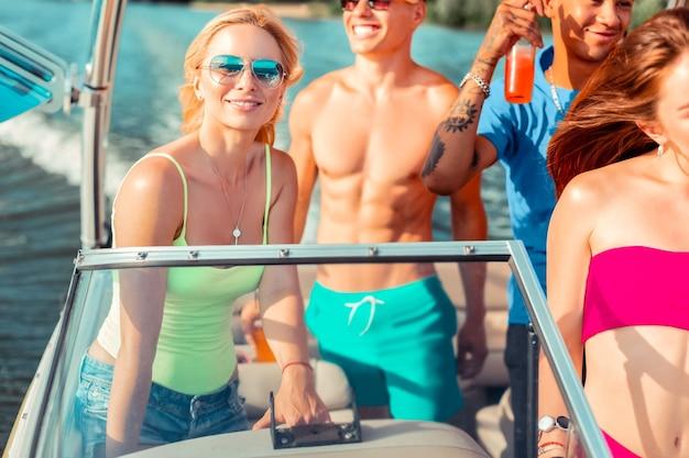 Jazda na łodzi. zbliżenie portret atrakcyjnej blondynki dziewczyny stojącej za kierownicą na jachcie w towarzystwie szczęśliwych przyjaciół patrzących w przyszłość