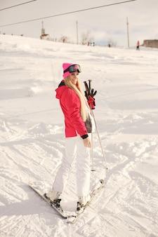 Jazda na nartach w górach. jasny kolor odzieży narciarskiej. dziewczyna spędza czas na nartach.