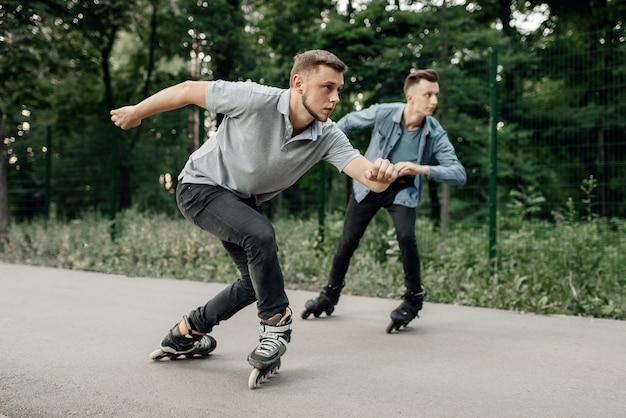 Jazda na rolkach, dwóch łyżwiarzy płci męskiej rozpoczyna wyścig prędkości w letnim parku. miejska jazda na rolkach, aktywny sport ekstremalny na świeżym powietrzu, jazda na rolkach