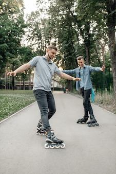 Jazda na rolkach, dwóch męskich łyżwiarzy toczących się w letnim parku. miejska jazda na rolkach, aktywny sport ekstremalny na świeżym powietrzu, jazda na rolkach