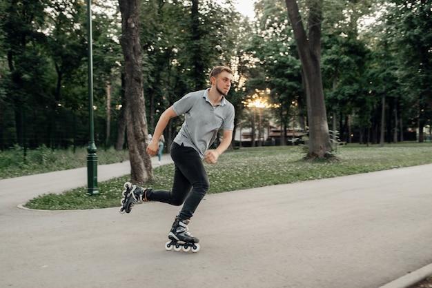 Jazda na rolkach, mężczyzna łyżwiarz toczący się w akcji. miejska jazda na rolkach, aktywny sport ekstremalny na świeżym powietrzu, wypoczynek młodzieży, jazda na rolkach