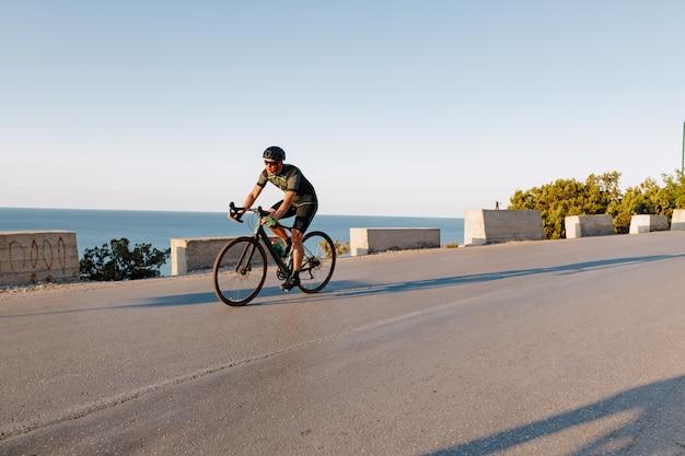 Jazda na rowerze sportowiec mężczyzna jedzie na nadmorskiej drodze o świcie
