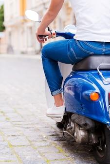 Jazda na skuterze. widok z tyłu przycięty obraz młodego mężczyzny jadącego skuterem wzdłuż ulicy