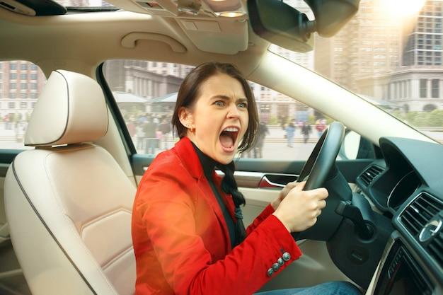 Jazda po mieście. młoda atrakcyjna kobieta podczas prowadzenia samochodu. młody całkiem kaukaski model w eleganckiej stylowej czerwonej kurtce siedzi w nowoczesnym wnętrzu pojazdu. koncepcja interesu.