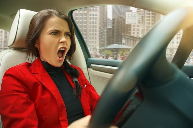 Jazda po mieście. młoda atrakcyjna kobieta podczas prowadzenia samochodu