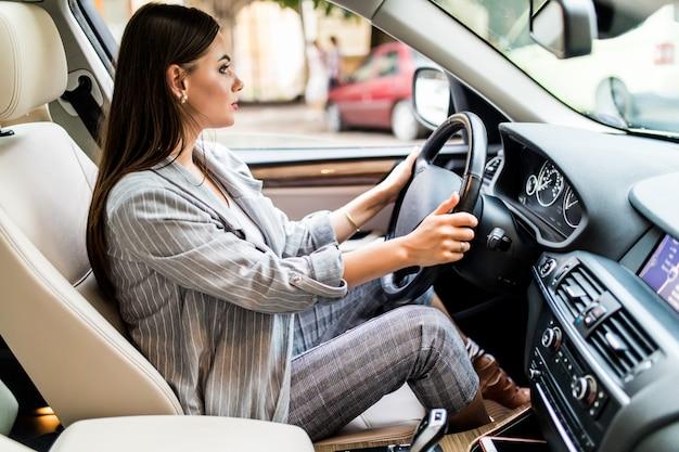 Jazda po mieście. młoda atrakcyjna kobieta uśmiecha się i patrząc prosto podczas prowadzenia samochodu
