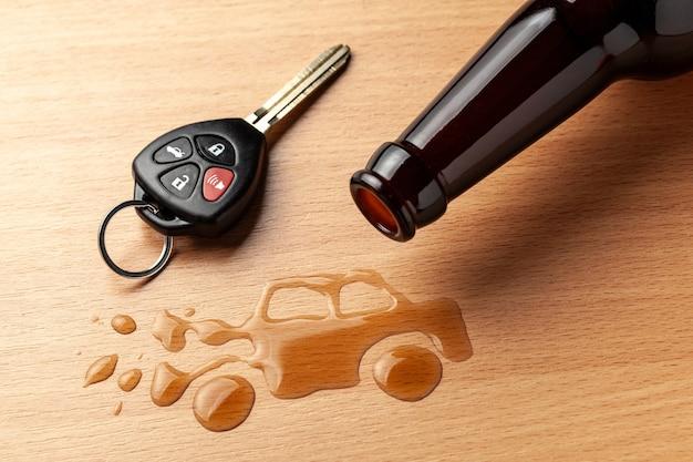 Jazda po pijanemu. wypadek z rozbitym samochodem od alkoholu. butelka piwa i kluczyki do samochodu. zepsuty samochód.