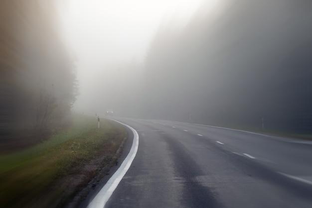 Jazda po wiejskiej drodze we mgle. ilustracja niebezpieczeństw związanych z jazdą w złych warunkach pogodowych: mglisto, trudno dostrzec z przodu