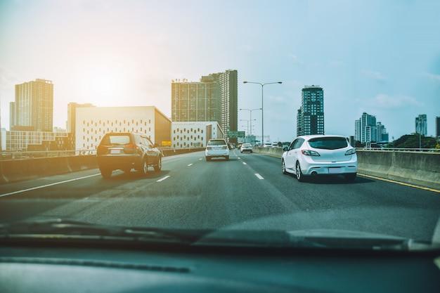 Jazda samochodem na drodze autostradowej, samochód zaparkowany na drodze i małe siedzenie samochodu osobowego na drodze używanej do codziennych podróży