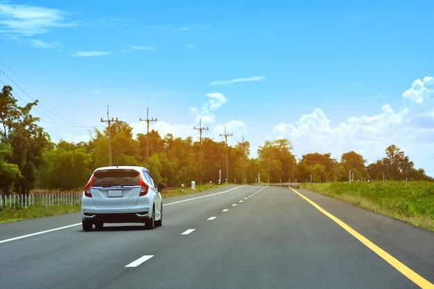 Jazda samochodem po drodze i mały fotelik samochodowy na drodze używany do codziennych podróży