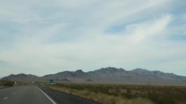 Jazda samochodem, trasa do las vegas, nevada usa. wycieczka samochodowa z wielkiego kanionu w arizonie. autostopem podróże po ameryce, dzikie ziemie indii, pustynie i góry. wilderness przez okno samochodu.