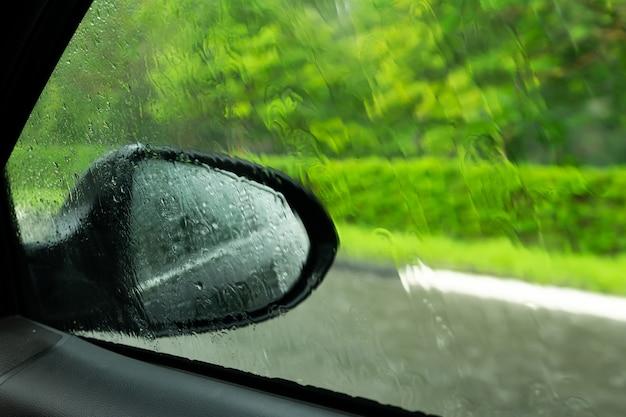Jazda samochodem w deszczu na mokrej drodze. deszczowa pogoda przez okno samochodu. deszcz przez przednią szybę jadącego samochodu. widok przez okno samochodu w deszczu. wycieraczki samochodowe włączone w deszczu.