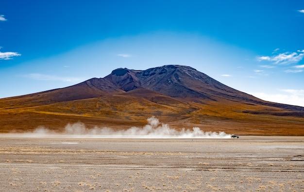 Jazda samochodem wśród pustyni na tle wysokiej boliwijskiej góry