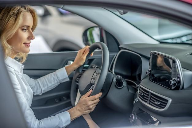 Jazda testowa. blondynka ładna kobieta siedzi w samochodzie przed jazdą próbną