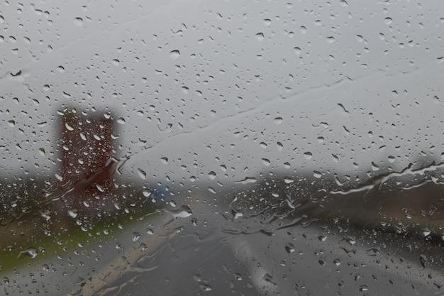 Jazda w deszczu. kropla deszczu na szybie samochodu. streszczenie ruchu w deszczowy dzień. widok z fotelika samochodowego. widok drogi przez okno samochodu z kroplami deszczu, selektywna ostrość.