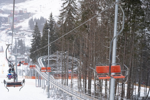 Jazda wyciągiem krzesełkowym przez las w górach z drzewami pokrytymi śniegiem. koncepcja wakacji