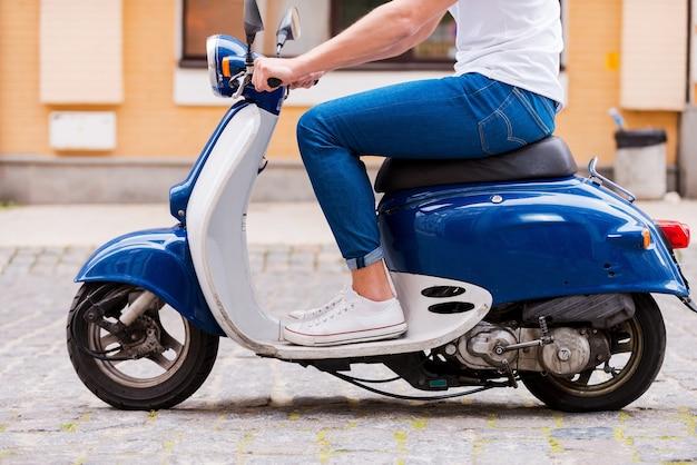 Jazda wzdłuż ulicy. widok z boku przycięty obraz młodego mężczyzny jadącego skuterem wzdłuż ulicy